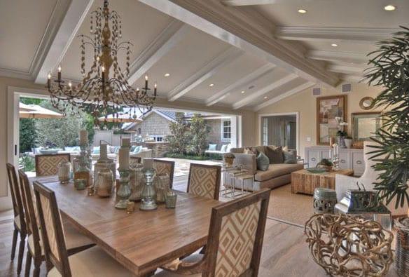 großszügises wohnesszimmer im beige mit panoramafenster und zugang zum garten, moderner einrichtung mit massibholzesstisch,kronleuchter, polstersofa und sessel in hellgrau, holzcouchtisch rechteckig