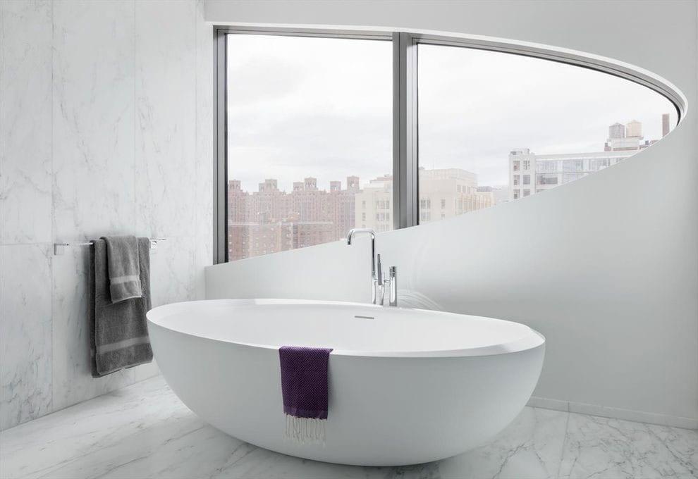 stilvolles baddesign mit weißem marmorfliesen, freistehender badewane oval und gerundetem fenster