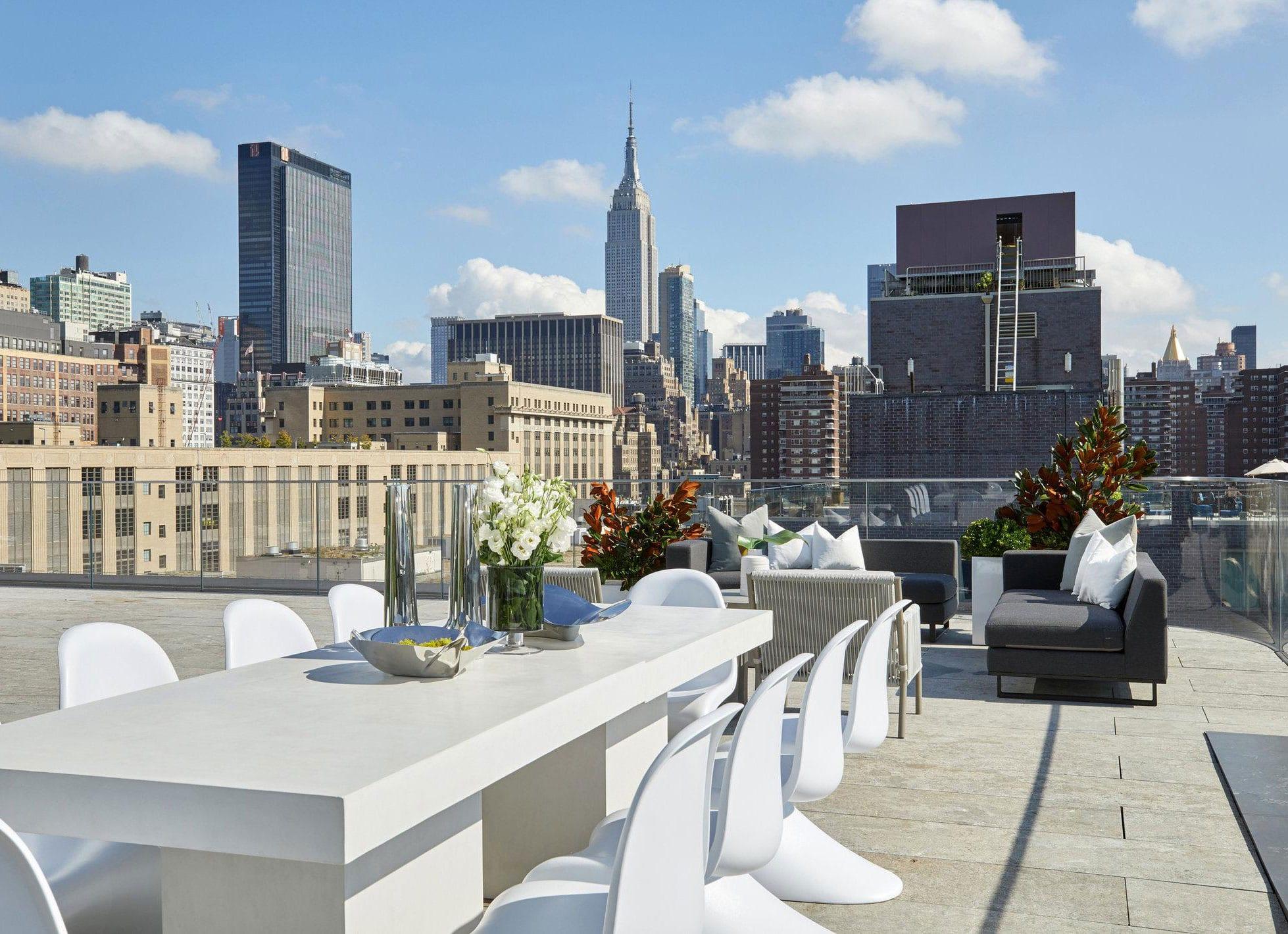 moderne terrassengestaltung einer dachterrasse mit glasgeländer, kuschelige sitzecke mit polstersofas und essgruppe mit massivem esstisch weiß und designer-esstischstühlen