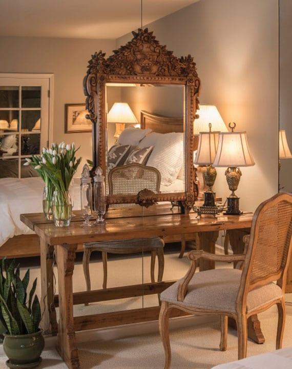 gemütliche schlafzimmerausstattung mit antiken holzmöbeln_stilvolle raumgestaltung mit spiegelwand, rustikalem schminktisch mit spiegel aus massivholz, vintage-tischlampe und barock-stuhl