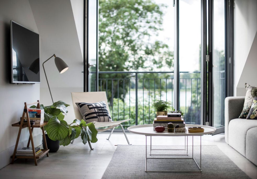 kleines wohnzimmer mit balkon wohnlich gestalten mit weißem metlallcouchtisch rund auf teppich grau, sessel-stuhl beige, moderner stehlampe weiß, zimmerpflanze im schwarzen blumentopf, holzbeistelltisch unter fernseher an der wand