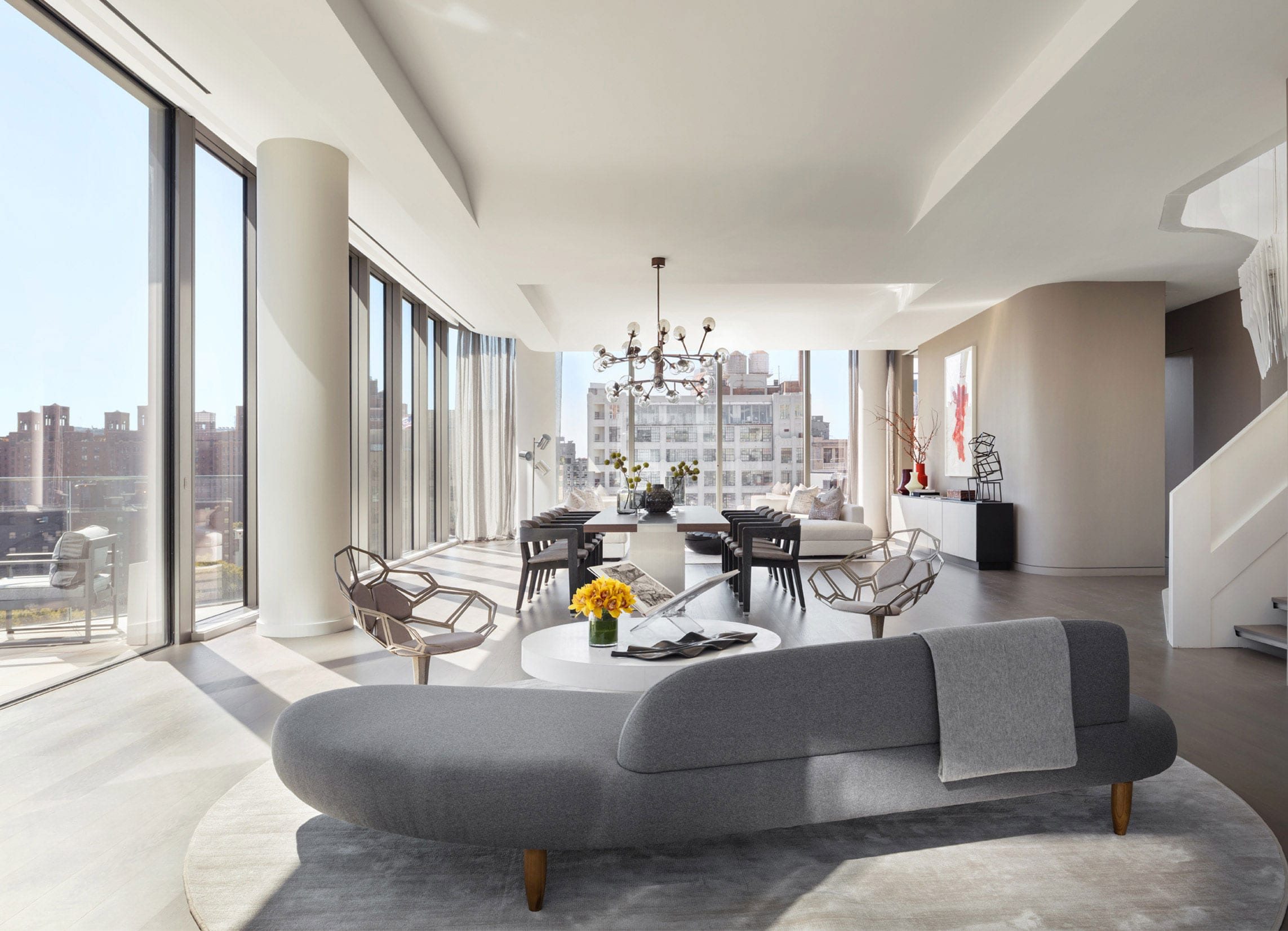 stilvolles wohnesszimmer mit bodentiefen fenstern, designer polstersofa mit rundem kaffeetisch und modernen stühlen, esstisch für 12 personen und zurückhaltender farbgestaltung in beige, weiß und holz