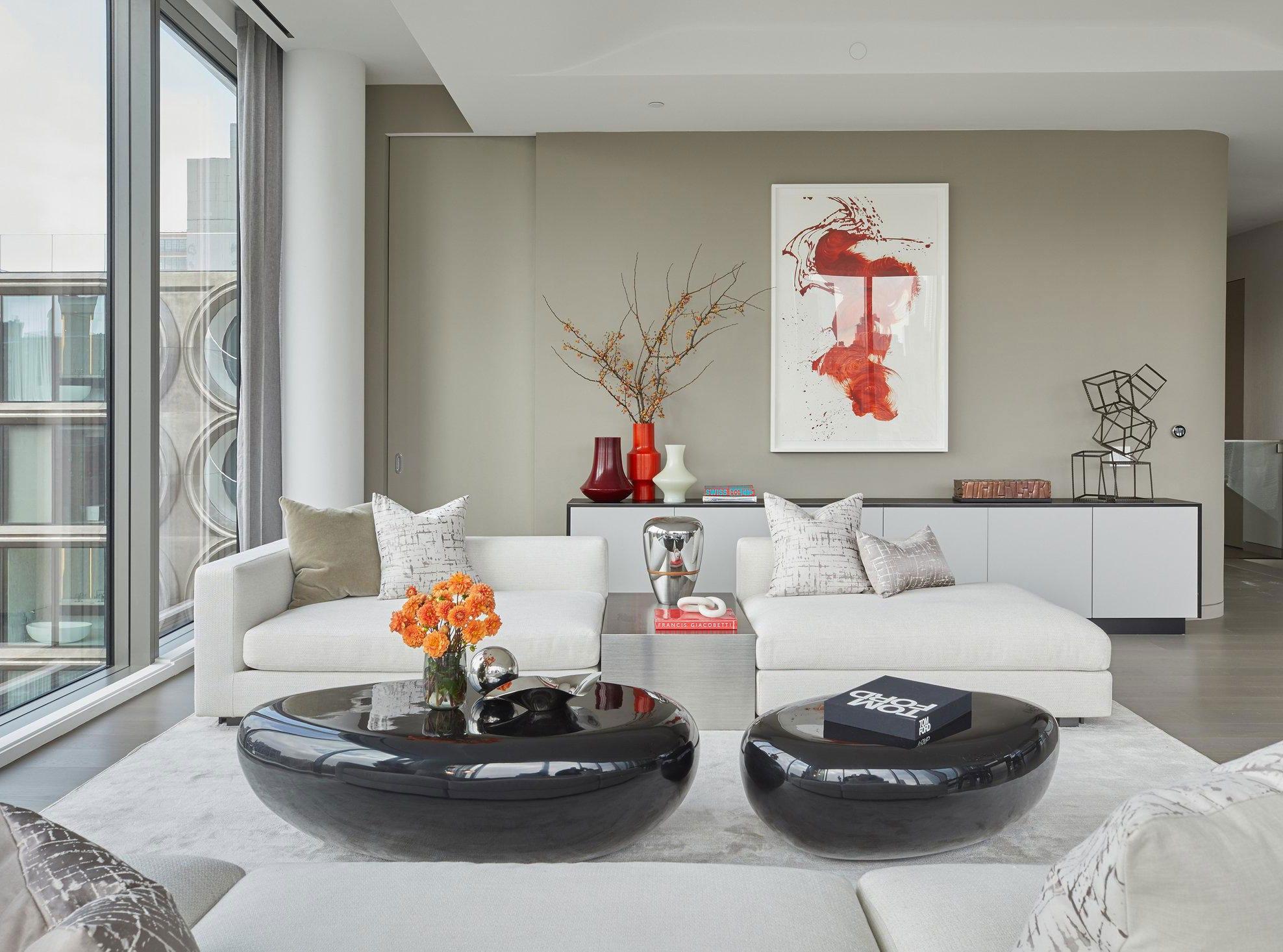 elegante raumgestaltung mit roten farbakzenten und kuscheligen sofas mit gerundeten couchtischen schwarz fürs wohnzimmer in weiß und beige