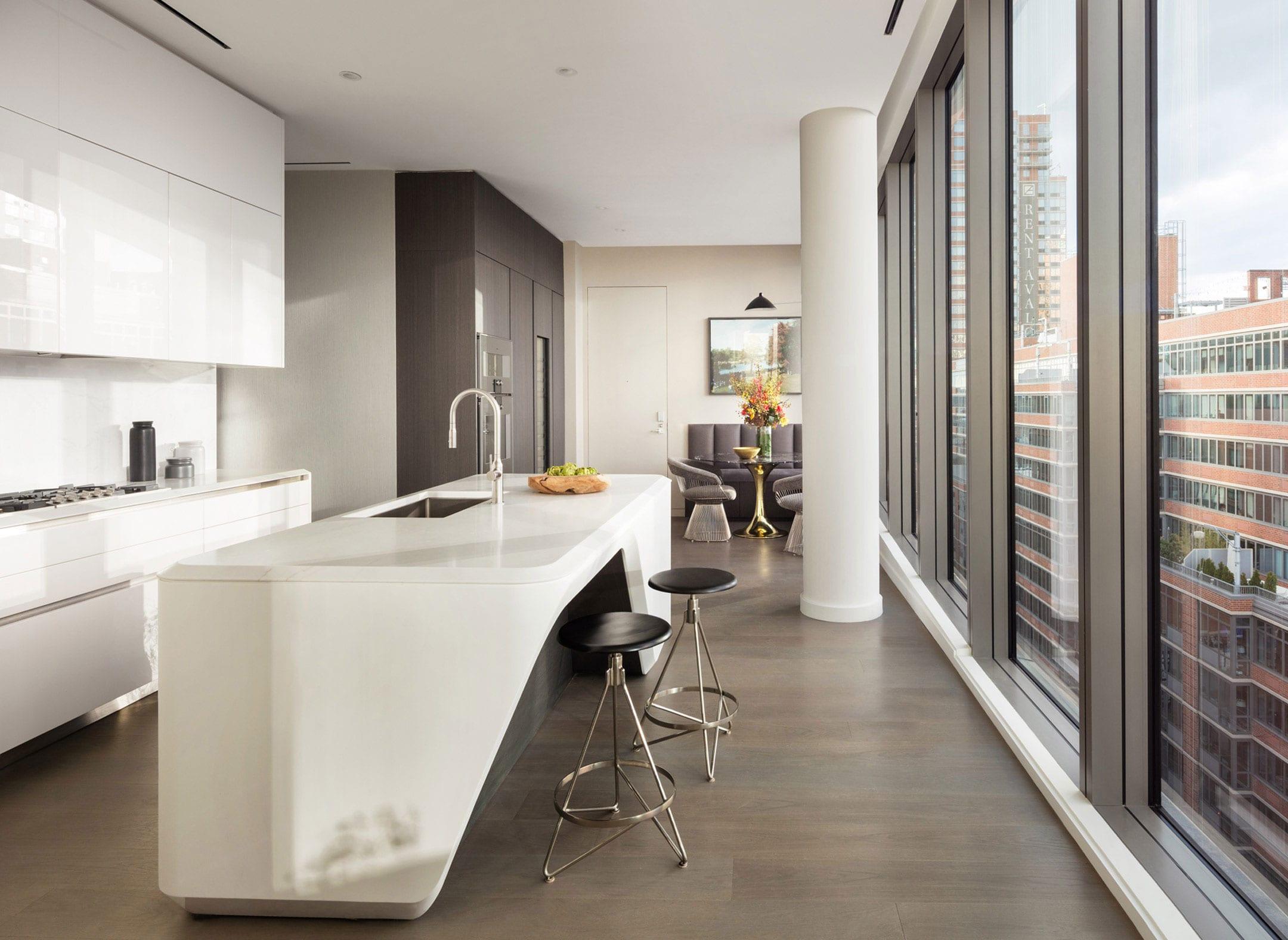 attraktive küche in weiß mit moderner corian-kochinsel und theke mit zwei rundem hockern, kleiner sitzecke mit rundem esstisch und polstersofa braun, einbauschränken in dunkelholz und panoramablick