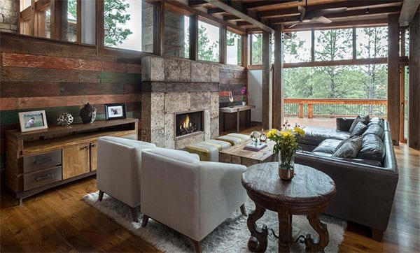 einladende hauseinrichtung in holz mit gemütlicher sitzecke im wohnzimmer mit kamin, ledersofa grau, holzcouchtisch, rustikalem holzbeistelltisch rund und sideboard aus massivholz