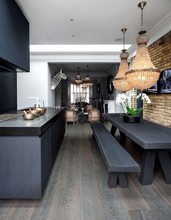 attraktive raumgestaltung für wohnzimmer mit holzküche in schwarz, essgruppe mit tisch und sitzbönken aus massivholz, akzentwand ziegel, indirekter deckenbeleuchtung und kristall-deckenleuchten