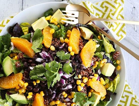 leckerer detox-salat mit avocado, orangen, koriander, zwiebel, schwarzen bohnen und limettendressing als gesundes mittagsessen