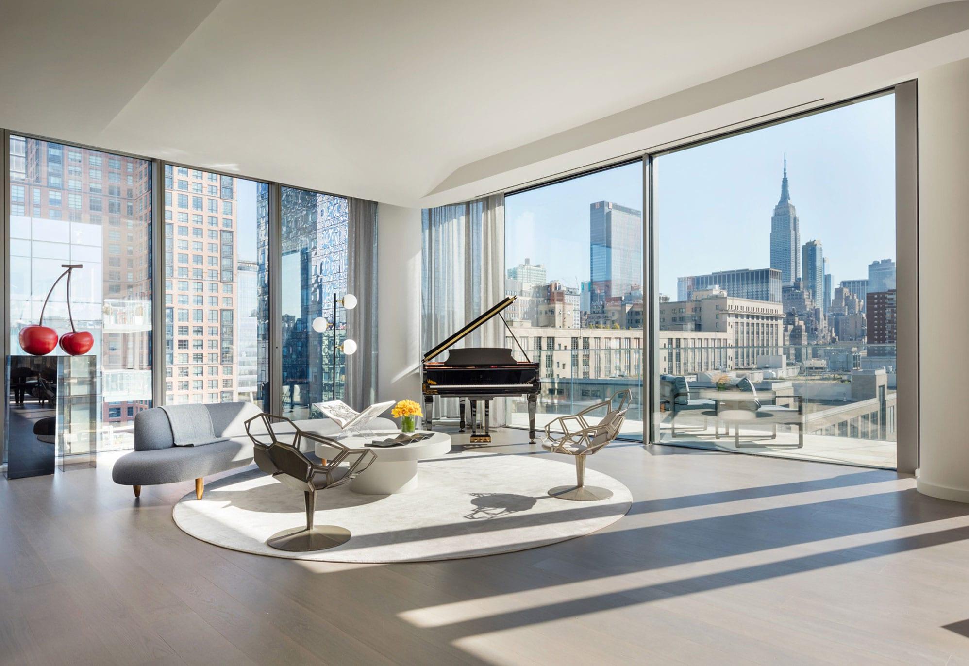 helles wohnzimmer mit stilvoller einrichtung einer sitzecke mit gerundetem sofa grau, designer drehstühle aus metall und rundem couchtisch weiß auf rundem teppich weiß, klavier und glasschiebetür zu balkon mit glasgeländer