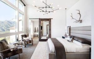 stilvolles schlafzimmer interioeur design in weiß und beige mit doppelbett und bettkopfteil aus leder, holzsessel mit pelz, rustikaler spiegel-schiebetür holz, moderner deckenleuchte schwarz und vintage-wanddeko mit geweih