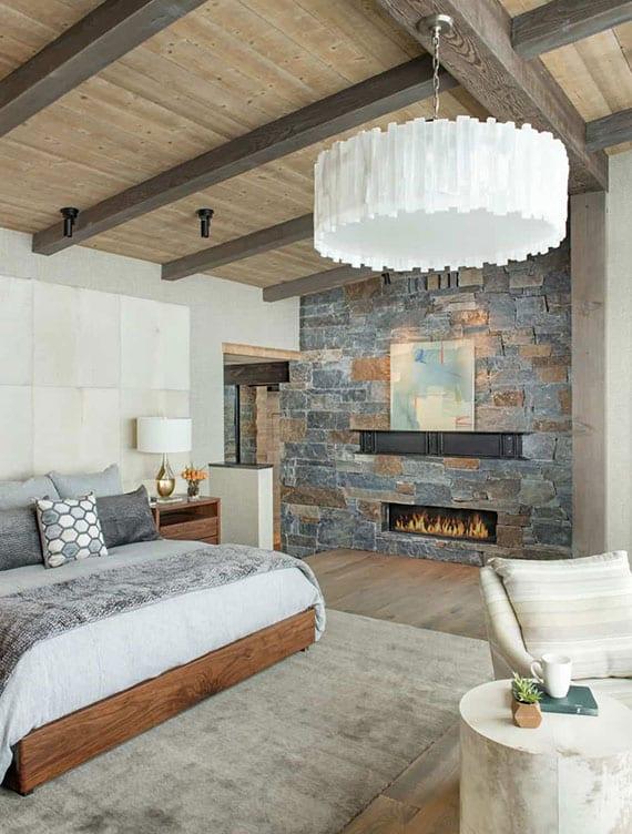 luxuriöses schlafzimmer intereur mit kamin, akzentwand aus natursteinplatten,gepolstertem kopfteil in weiß, holzbett mit nachttisch aus holz,bettdecke und kissen in grau, holzdecke mit moderner hängelampe weiß