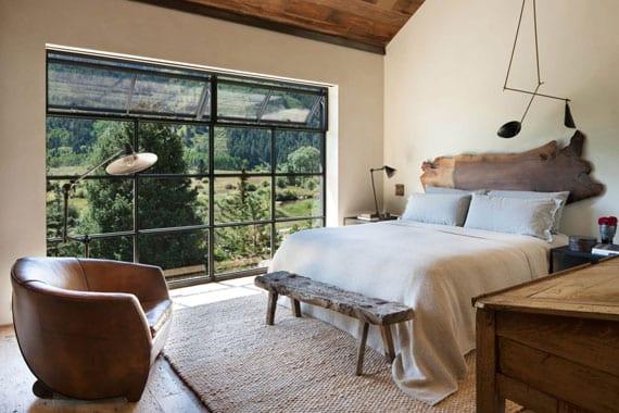 kleines schlafzimmer mit dachschräge und panoramablick rustikal einrichten mit alter Holzbank vor doppelbett mit Kopfteil aus massivholz, ledersessel braun, vintage-holzschreibtisch, designer-pendellampe und holzdeckenverkleidung