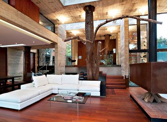modernes interieur mit sichtbetonwänden, holzbodenbelag, holzwandverkleidung, deckenkamin vor weißem ledersofa mit glascouchtisch und böumen als dekorative stützen