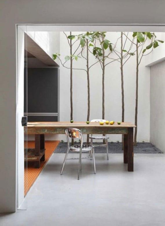 coole idee für moderne küchengestaltung im rustikalen stil mit holzesstisch, metalstühlen und oberlichter über baumgarten im kiesboden