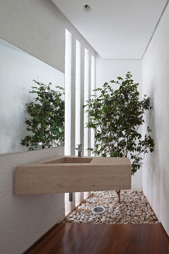 coole bad idee für attraktive und moderne badgestaltung mit baum im kiesboden, natürluche raumbeleuchtung durch schmale wandöffnungen, naturstein waschbecken, betonwand und holzbodenbelag