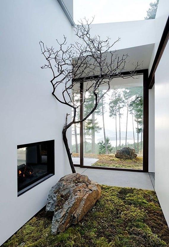 ein kleiner moos-garten mit baum und felsen im innenraum gestalten unter oberlicht und mit blick aufs wohnzimmer durch doppelseitigen kamin