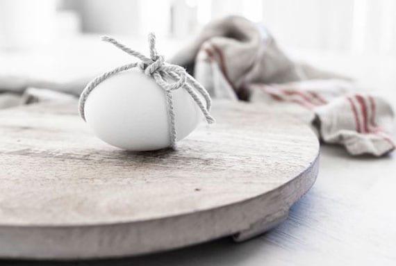 atraktive und schlichte osterdekoration_weiße ostereier mit bindfaden dekorieren und auf rundem holzschneidebrett arrangieren