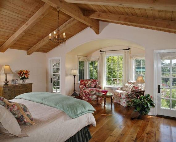 schöne schlafzimmer unter holzdachschräge mit parkettboden,wandfarbe weiß, weißen holzfenstern mit sprossen, polstersesseln mit floralem muster, rundem beistelltisch und holzkommode