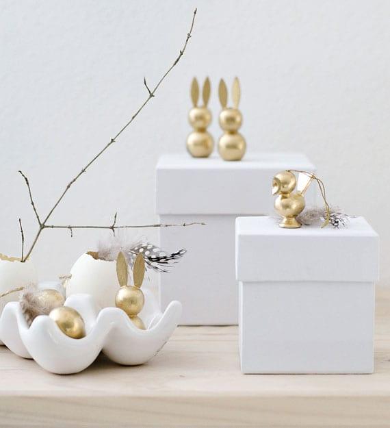 coole ostern ideen für moderne osterdeko im skandinavischen stil mit goldenen osterhasen,zweigen,kleinen weißen geschenkboxen und keramik-eierhalter