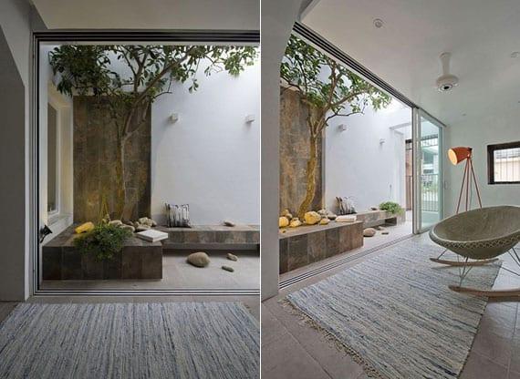 attraktive balkongestaltung mit akzentwand und ecksitzbank aus naturstein, baum im hochbeet und kleinem steingarten
