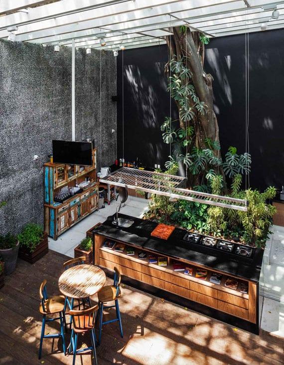 moderne und wohnliche raumgestaltung einer metzgerei mit schwarzer akzentwand,kleinem innengarten und rustikaler holzmöblierung unter holzpergola und dach mit oberlichtern