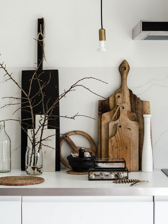 moderne skandinavische osterdekoration für weiße küche mit holzschneidbrettern, zweigen im glas, wachteleiern im glasbox, weiden-untersetzer, schneidebrett und mörser in schwarz