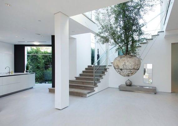 attraktive zimmerdeko mit einem baum und coole gestaltungsideen für moderne und offene wohnzimmer mit wohnküche und offener innentreppe
