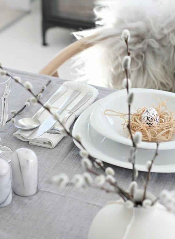 tisch elegant eindecken zu ostern in grau und weiß mit kleinem stroh-osternest im teller und vase mit weidenkätzchen-zweigen
