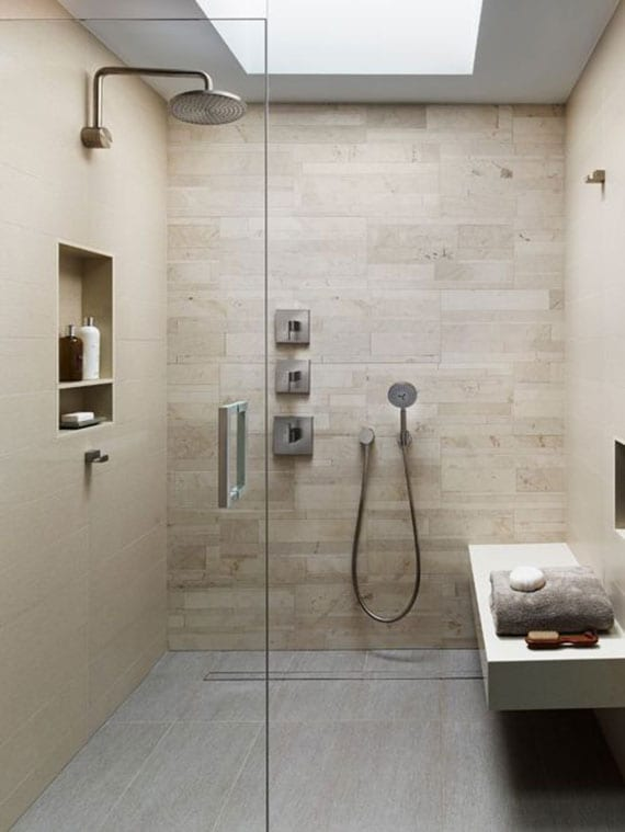 modernes badezimmer mit deckenlicht, wandfliesen in beige, bodengleicher dusche mit glastüren und sitzbank weiß, einbaiwandregalen