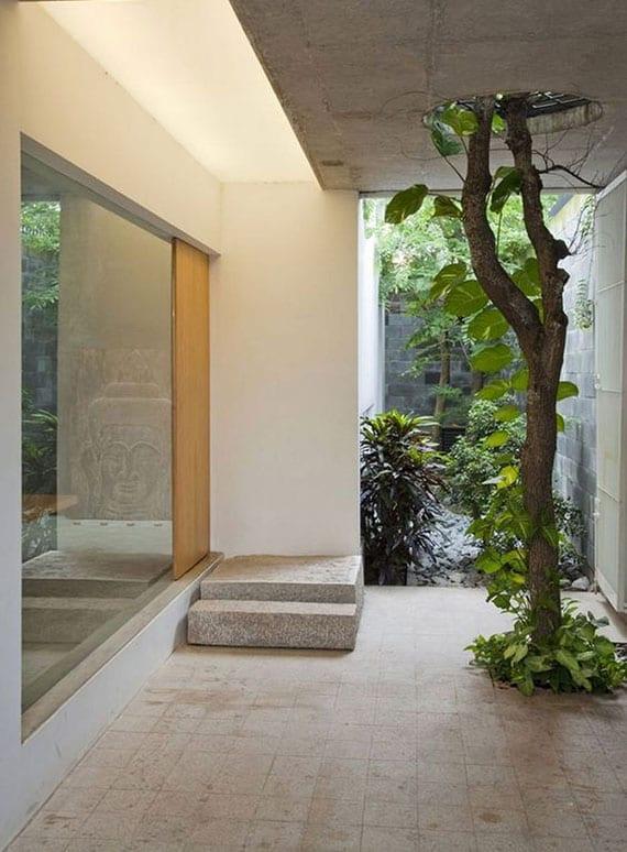moderne gestaltung vom hauseingang mit überdachter terrasse und baum vor panoramafenster mit holztür und indirekter deckenbeleuchtung