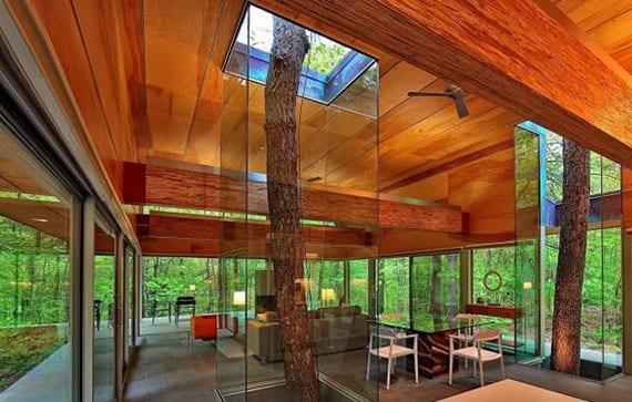 modernes glashaus im wald mit holzdecke und betonboden_offenes wohn-esszimmer mit bäumen in glasschächten