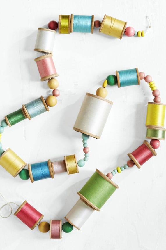 originelle und einfache upcycling-idee mit bunten fadenspulen und holzkugeln
