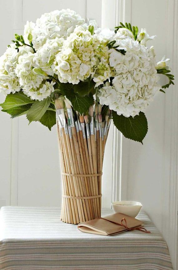 frische tischdeko mit weißen frühlingsblumen in diy Vase aus Holzpinseln