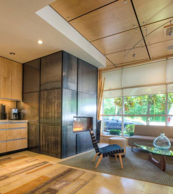 effektvoles und wohnliches Interieur gestalten mit wandpaneelen in Metalloptik und deckenpaneelen holz_ wohnesszimmer mit holzküche, einbaukamin,tiefbodenfenster,sitzecke mit holzsessel, glascouchtisch und polstersofa grau