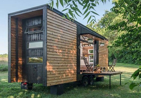 kleines vorgefertigtes haus aus holz mit kleiner terrasse, küche und hochbett