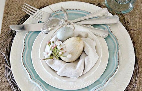 rustikale tischdeko ostern mit kranz aus weinreibe, vinatge-tellern in hellblau und weiß, osternest aus stoffserviete mit blüten und holzei