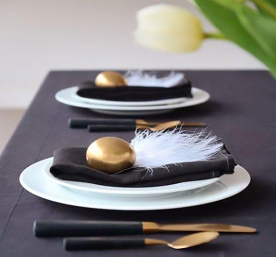 moderne ostertischdeko mit schwarzen stoffservieten, goldenen ostereiern und weißen federn als stilvolle platztellerdeko