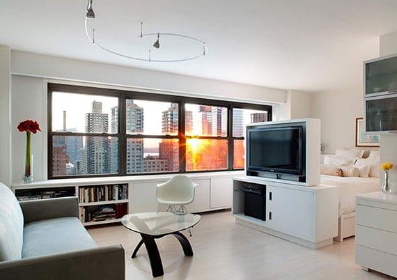 1-Zi-Apartment luxuriös einrichten mit einbauschrank weiß unter fensterbank, schlafbereich im wohnzimmer mit drehebarem tv-schrank als raumteiler zwischen sofa und bett