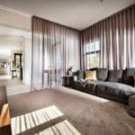 luxus wohnzimmer in braun mit polstersofa, holz tv-schrank, hochfloorteppich und gardine als raumtrenner