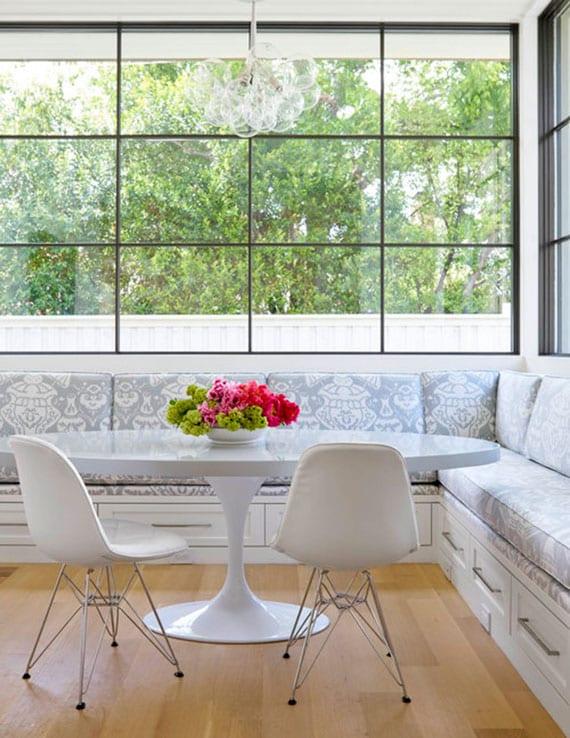 esszimmer elegant und praktisch einrichten sitzecke aus ecksitzbank vor dem fenster mit gemusterten sitzkissen und schubladen, rundem esstisch weiß und designer esszimmerstühlen aus leder