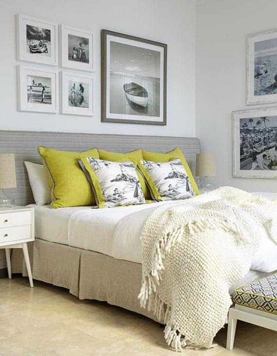 attraktive schlafzimmer idee für moderne und stilvolle raumgestaltung mit schwarzweißen fotos in holzbilderrahmen, sitzbank weiß vor bett mit polsterkopfteil in beige, dekokisen in grün und strickdecke in creme