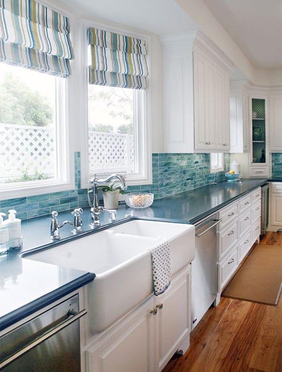 klassische küche in weiß und blau mit Raffrollos als passender Dekor und Sonnenschutz, Retro-Küchenspüle aus Keramik mit Retro-Standbaterie