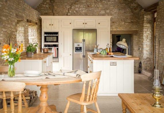 stilvolle mediterrane küche mit steinmauern, weißen küchenschränken und kochinsel, rundem esstisch miit holzstühlen im landhausstil