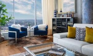 stilvolle raumgestaltungsidee für modernes wohnzimmer interieur mit blauen polstersesseln auf kuhfell-teppich und gebe dekokissen als farbakzent zum ledersofa in beige