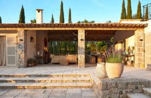 mediterranische terrassengestaltung mit naturstein, überdachung, pflanzen in grüßen runden keramikkübeln, rattan-gartenmöbeln und kamin