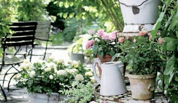 attraktive-gartengestaltung-im-vintage-stil-mit-pflasterboden-und-topfblumen-in-vitage-gefäßen