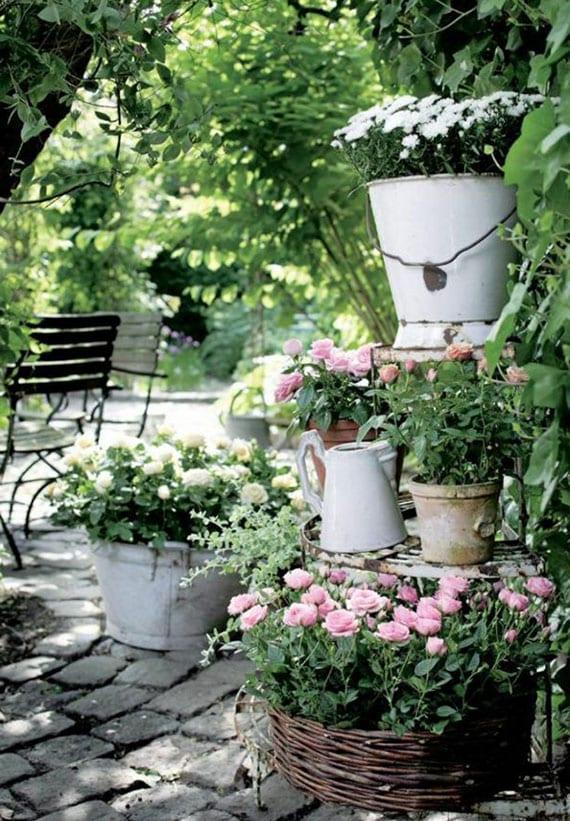 garten romantisch gestalten mit pflasterboden und kleinem rosengarten in metalleimern und weidenkörben