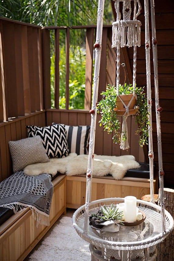 coole gestaltungsidee für außenbereich im boho stil mit rundem hängetisch, makramee-ampel, holzbank mit dekokissen und wohntextilien in schwarz und weiß