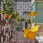 originelle ideen für bunte und attraktive balkongestaltung mit rattanschaukelstuhl gelb, rundem esstisch mit orangen stühlen, balkonerweiterung durch metallgitter als sichtschutz und schtürzschutz