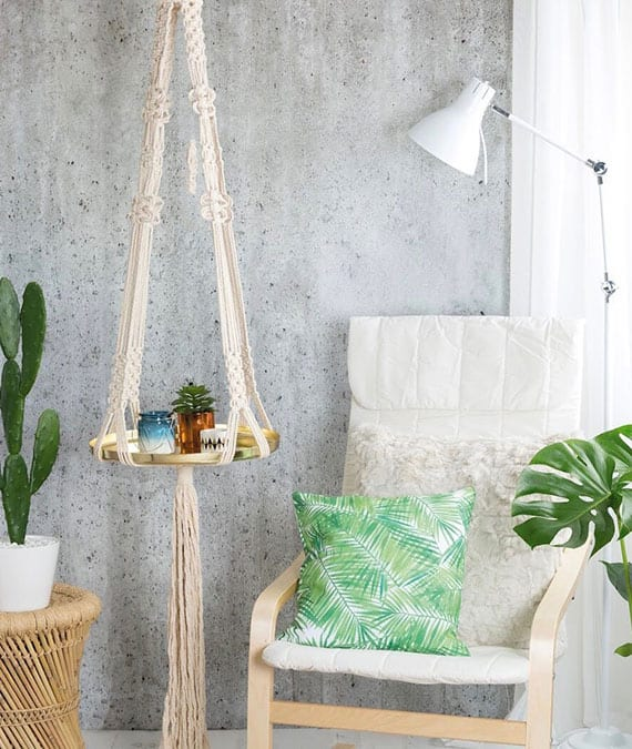 stilvolle gestaltung einer gemütlichen sitzecke mit schaukelstuhl, hängendem makramee-beistelltisch mit runder metallschale,stehelampe weiß und grünen pflanzen in weißen blumentöpfen