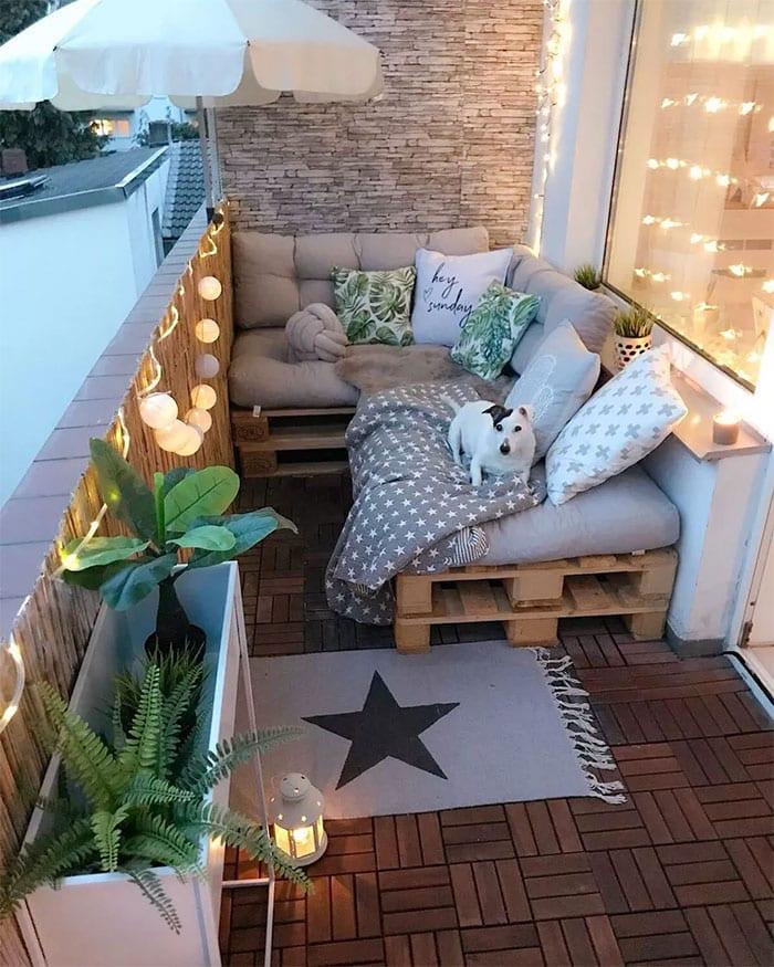 kleiner balkon mit akzentwand aus naturstein,diy ecksofa aus paletten, grauen sitzkissen, holzdeckplatten, pflanzen in weißem blumenkasten, schilfzaun als sichtschutz, lichterkette und sonnenschirm weiß